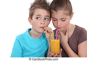 Children drinking a glass of orange juice