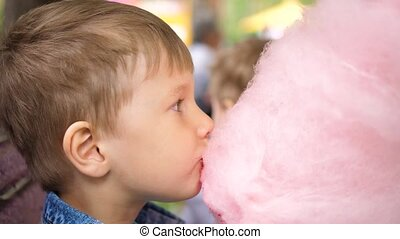 Children eat cotton candy in the Park. Sweet and airy...