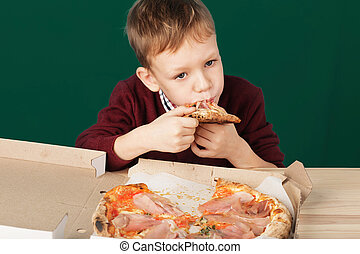 Children eat Italian pizza in the cafe. School boy is eating pizza for lunch. Child unhealthy meal concept. Hungry kids. Pizza recipe.
