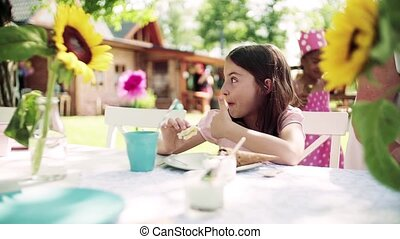 Children eating icecream on birthday party outdoors in garden in summer. Slow motion.