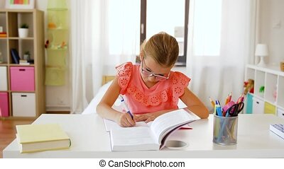 student girl with book writing to notebook at home -...