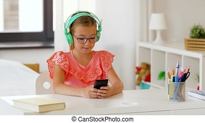 girl in headphones with smartphone at home - children,...