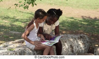 Young people and education, two little girls reading book in city park