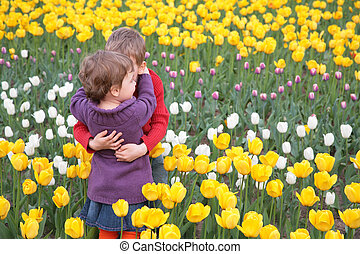 Children embrace each other on  field of tulips