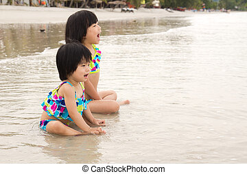 Children enjoy waves on beach