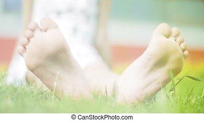 Children feet on green grass