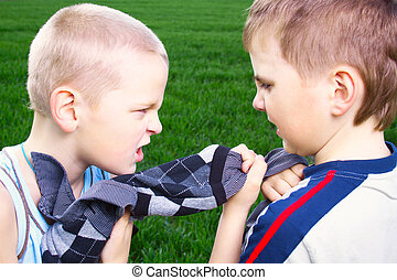 Children fighting over a sweater on a green field