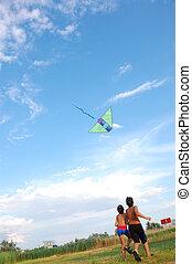 children flying kite in the sky