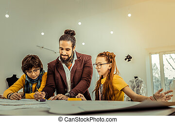 Children fond of designing listening to their teacher at master class