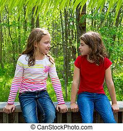 children friend girls talking on the jungle park forest