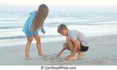 Children friends boy and girl drawing on sand.