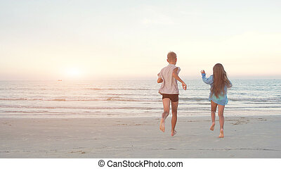 Children friends boy and girl running into the sea