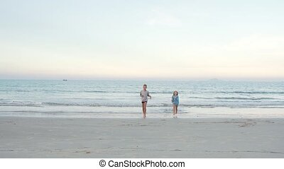 Children friends boy and girl running out of the sea