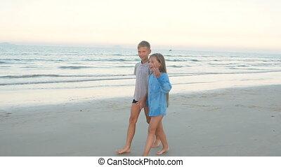 Children friends boy and girl walking along the beach