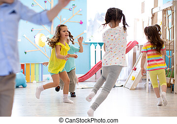 Children games in playroom. Kids play and run.