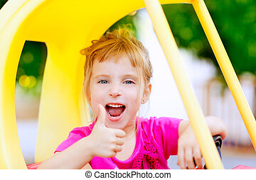 girl driving toy car with ok hand gesture