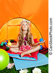 Children girl inside camping tent relaxing with yoga