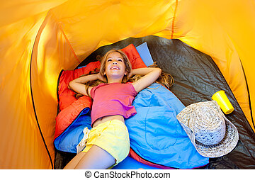 Children girl lying on camping tent floor in vacation
