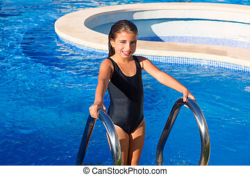 children girl on the blue pool stairs with black swimsuit in summer vacations