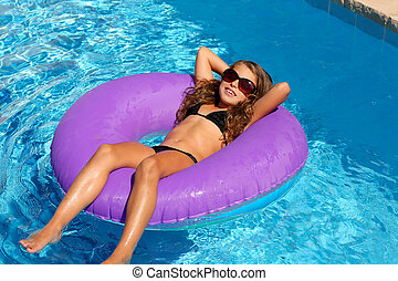 children girl relaxed on purple inflatable pool ring
