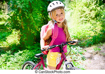 Children girl riding bicycle outdoor in forest smiling with...