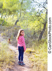 children girl walking in the pine forest with dog