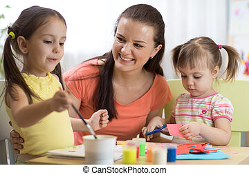 children girls and mother hands making at nursery at home