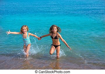 children girls friends running together in the beach shore