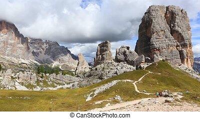children girls hikers walking near of Cinque Torri towers...