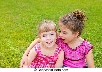 children girls hug in green grass park