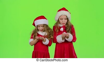 Children girls in the Christmas costumes inflate the stellar...