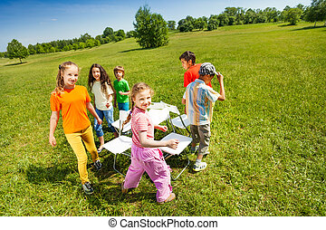 Children go around playing musical chairs outside