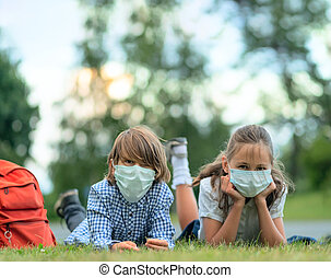 Children go back to school. Cute pupils with backpacks. Boy and girl in safety masks lie on the grass