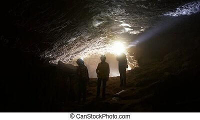 Children go through the cave - Two girls and a boy go on a...
