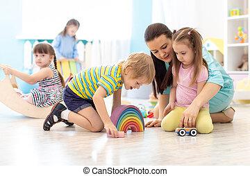 Children group playing in kindergarten. Kids with teacher in classroom