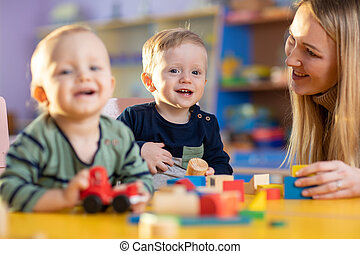 children group playing with teacher in day care centre playroom