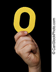 Children hand holding the number Zero. Black isolated yellow...