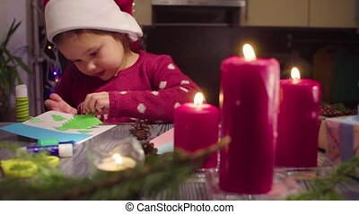 Little girl glues New Year card
