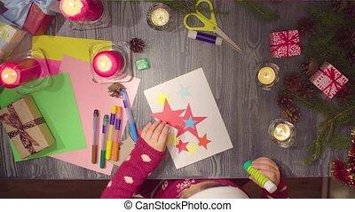 Children handicraft. Little girl glues New Year card - Top...