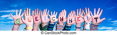 Children Hands Building Colorful German Word Gleichheit Means Equality. Blue Sky As Background
