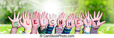 Children Hands Building Colorful German Word Gleichheit Means Equality. Sunny Green Grass Meadow As Background