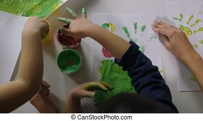 Children hands finger painting with various colors
