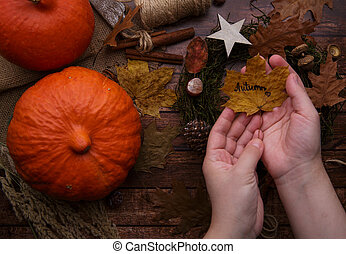 Children hands with a yellow leaf on the background of an autumn wreath