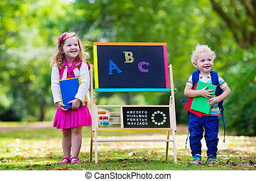 Children happy to be back to school. Preschooler girl and...