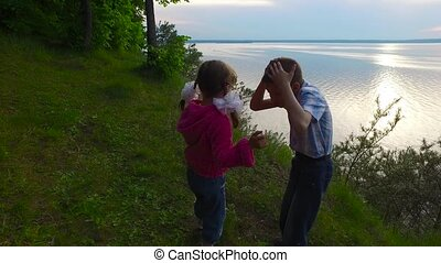 Children have fun in the forest on the shore of a large lake. The children ate fruit. They have a good mood. They are having fun. Evening in the summer forest.