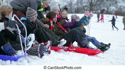 Children Having a Sled Race - Children are lined up at the...