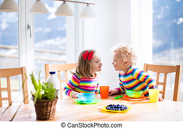 Children having breakfast in sunny kitchen