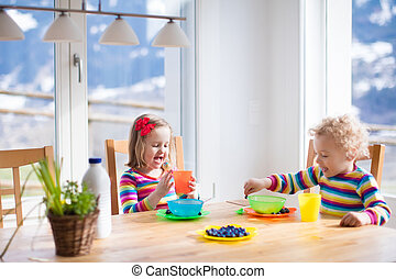 Children having breakfast in sunny kitchen
