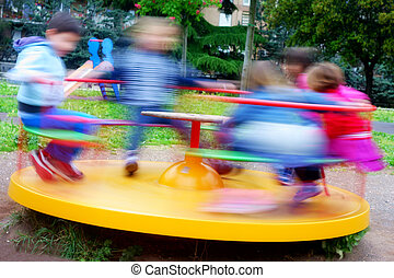 children having fun at colorful carousel spinning round fast