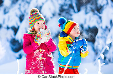 Children having fun in snowy winter park